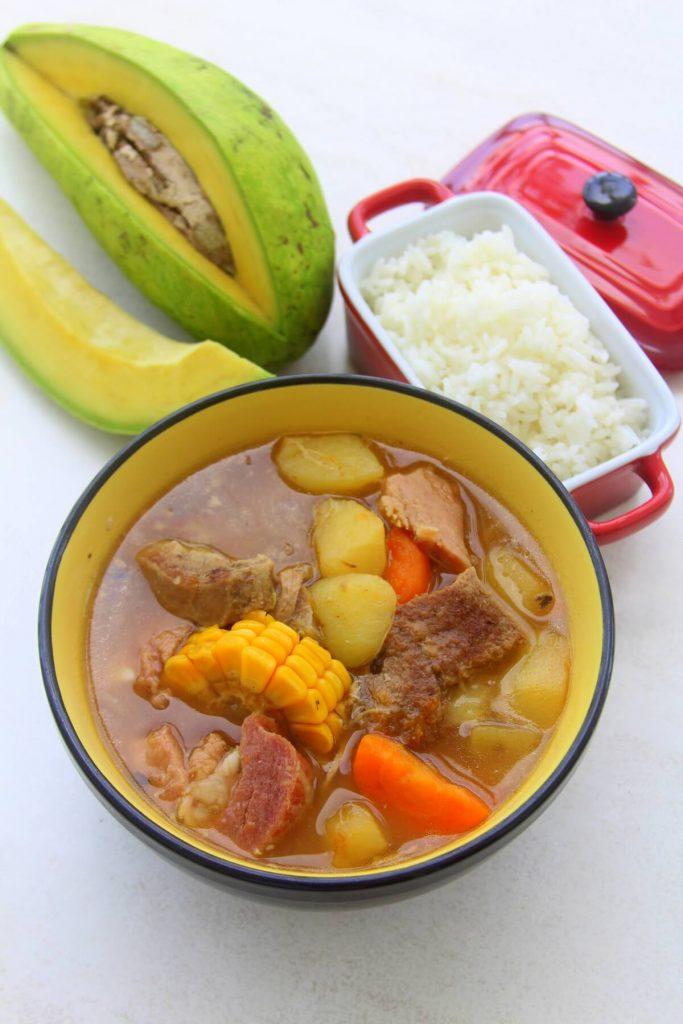 Plato de asopao dominicano con arroz blanco y aguacate